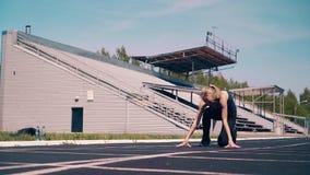 Młoda dziewczyna, sporty budowa ciała przy stadium, Iść początek linia, dostaje w niskiego początek zbiory