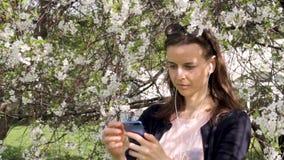 Młoda dziewczyna sprawdza jej wiszącą ozdobę outdoors zdjęcie wideo