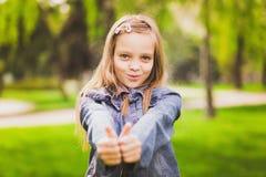 Młoda dziewczyna stawia jej duże aprobaty zdjęcia stock
