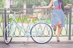Młoda dziewczyna stoi blisko płotowego pobliskiego rocznika roweru przy parkiem Obraz Stock