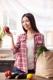 Młoda dziewczyna stoi blisko torby z produktami trzyma jabłczaną przyglądającą kamerę rozochocona przy kuchennym zdrowym styl życ obrazy stock
