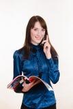 Młoda dziewczyna stojaki z magazynem i dzwonić na telefonie fotografia royalty free