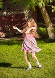 Młoda dziewczyna taniec na trawie przy słonecznym dniem Zdjęcie Stock