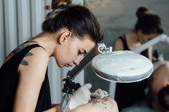 Młoda dziewczyna tatuażu mistrz z włosy wiążącym w wiązce w czarnym podkoszulku z tatuażem na plecy siedzi w profilu Zdjęcia Stock