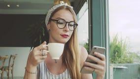 Młoda dziewczyna texting na telefonie komórkowym Kobieta używa gona na smartphone w cukiernianym i uśmiechniętym zbiory