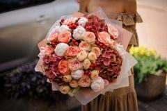 Młoda dziewczyna trzyma bukiet namiętni kwiaty Zdjęcia Stock