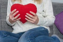 Młoda dziewczyna trzyma dużą czerwoną kierową poduszkę w ręce na jej klatce piersiowej i obsiadaniu na łóżku obrazy royalty free