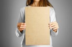 Młoda dziewczyna trzyma kawałek karton w białej kurtce Pre Zdjęcia Royalty Free
