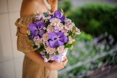 Młoda dziewczyna trzyma kosz fiołkowi kwiaty Obrazy Stock