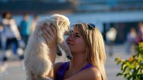 Młoda dziewczyna trzyma 3 miesięcy Labrador retriever starego szczeniaka, plenerowy, blured tło, zdjęcia royalty free