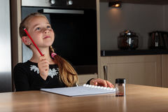 Młoda dziewczyna trzyma ołówek up znajdował rozwiązanie podczas gdy robić pracie domowej przy kuchennym stołem obraz stock
