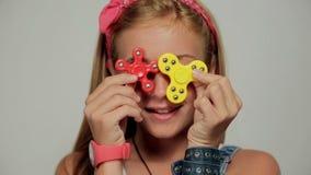 Młoda dziewczyna trzyma popularną wiercipięta kądziołka zabawkę - zamyka w górę portreta zdjęcie wideo