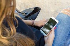 Młoda dziewczyna trzyma smartphone z malującymi gwoździami obraz royalty free