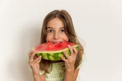 Młoda dziewczyna uśmiecha się dojrzałego arbuza i je zdrowe jeść Obrazy Royalty Free