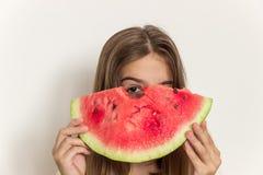 Młoda dziewczyna uśmiecha się dojrzałego arbuza i je zdrowe jeść Obraz Stock