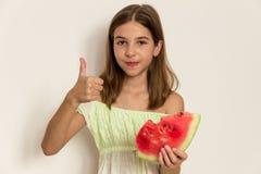 Młoda dziewczyna uśmiecha się dojrzałego arbuza i je zdrowe jeść Zdjęcia Royalty Free