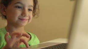 Młoda dziewczyna używa komputer dla pracy domowej