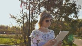 Młoda dziewczyna używa pastylkę plenerową i uśmiechniętą Dziewczyna używa cyfrowego pastylka komputer osobistego w parku Studenck zdjęcie wideo