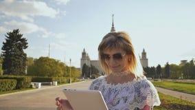Młoda dziewczyna używa pastylkę plenerową i uśmiechniętą Dziewczyna używa cyfrowego pastylka komputer osobistego w parku Studenck zbiory