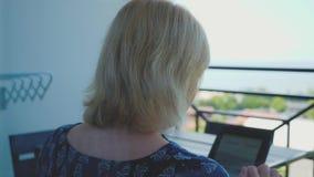 Młoda dziewczyna używa pastylki obsiadanie na leżance patrzeje w domu dla coś w online sklepie Zakupy, ogólnospołeczni środki zbiory