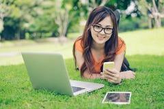 Młoda dziewczyna używa smartphone, pastylkę i laptop, zdjęcie royalty free