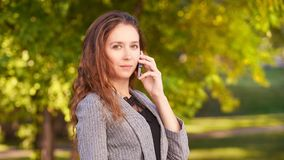 Młoda dziewczyna używa telefon komórkowego outdoors Młodości kobieta opowiada jak konsultant Gadka biznes obraz stock