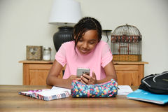 Młoda dziewczyna używa telefon komórkowego raczej pracuje Obraz Royalty Free
