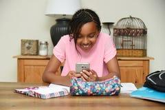 Młoda dziewczyna używa telefon komórkowego raczej pracuje Obraz Stock