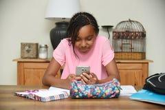 Młoda dziewczyna używa telefon komórkowego raczej pracuje Fotografia Royalty Free