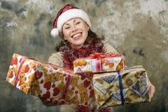 Młoda dziewczyna ubierający Święty Mikołaj z prezentów pudełkami Zdjęcia Stock