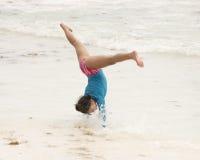 Młoda dziewczyna w środku cartwheel na plaży fotografia stock