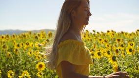 Młoda dziewczyna w żółtej sukni biega przez pole w słonecznikach swobodny ruch zbiory