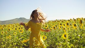 Młoda dziewczyna w żółtej sukni biega w słonecznikach swobodny ruch zbiory