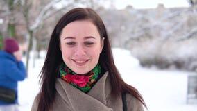 Młoda dziewczyna w żakiecie, spaceruje przez zima parka i pije kawę, podczas gdy patrzejący kamerę zdjęcie wideo