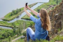 Młoda dziewczyna w błękitów ubraniach, jest ubranym okulary przeciwsłonecznych robi selfie w lecie outdoors obraz stock