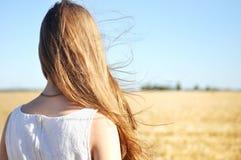 Młoda dziewczyna w białych suknia stojakach w wiatrze i polu trzepocze jej włosy Obrazy Royalty Free
