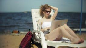 Młoda dziewczyna w białym bikini kłama, garbnikuje na deckchair na dennej piaskowatej plaży i pracuje na laptopie zbiory