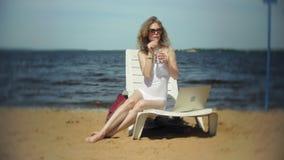 Młoda dziewczyna w białym bikini kłama, garbnikuje na deckchair na dennej piaskowatej plaży i pracuje na laptopie zdjęcie wideo