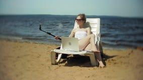 Młoda dziewczyna w białym bikini kłama i sunbathes na deckchair na dennej piaskowatej plaży i fotografiach na smartphone zbiory