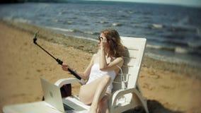 Młoda dziewczyna w białym bikini kłama i sunbathes na deckchair na dennej piaskowatej plaży i fotografiach na smartphone zdjęcie wideo