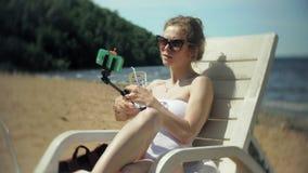 Młoda dziewczyna w białym bikini kłama i sunbathes na deckchair na dennej piaskowatej plaży i fotografiach na smartphone zbiory wideo