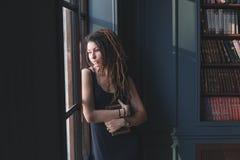 młoda dziewczyna w bibliotece, stoi okno w myśli Zdjęcie Royalty Free