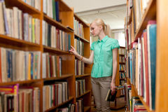 Młoda dziewczyna w bibliotece target525_0_ dla książki Zdjęcia Royalty Free