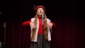 Młoda dziewczyna w Bożenarodzeniowym pojęciu śpiewa piosence frontowego retro mikrofon na ciemnej scenie zbiory wideo
