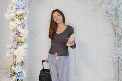 Młoda dziewczyna w brąz kurtce z biletami i paszport w jej ręk spojrzeniach przy kamerą, uśmiechamy się, niesiemy, walizkę obraz royalty free