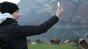 Młoda dziewczyna w czarnym kapeluszu i zimy kurtce robi selfi przeciw tłu Alps zdjęcie wideo