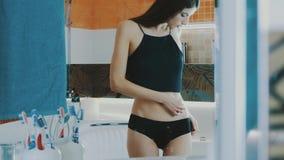 Młoda dziewczyna w czerń wierzchołka dotyka żołądku przed lustrem w łazience slimness zdjęcie wideo