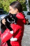 Młoda dziewczyna w czerwonej kurtce trzyma wielkich czarny i biały kotów wi Obrazy Stock