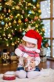 Młoda dziewczyna w czerwonych Santa otwarcia bożych narodzeń kapeluszowych prezentach Fotografia Royalty Free