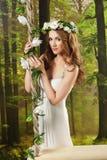 Młoda dziewczyna w długiej biel sukni z wiankiem na huśtawce w studiu, Zdjęcie Royalty Free